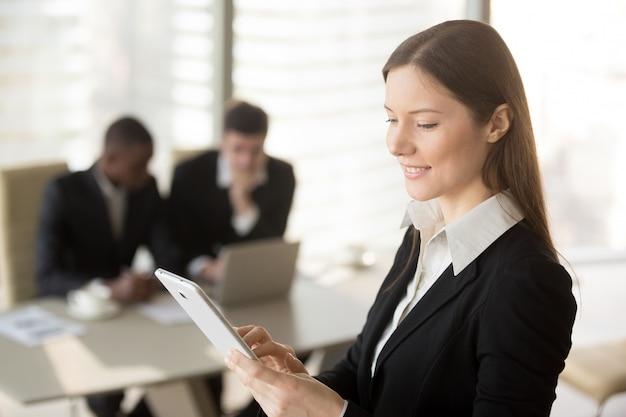 Empresaria atractiva joven que sostiene la tableta, mirando la pantalla