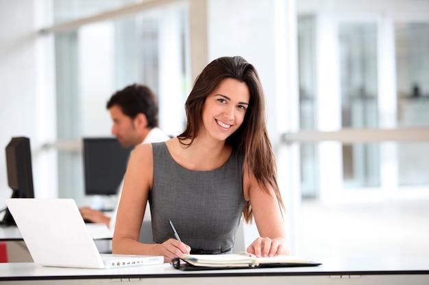 Empresaria atractiva que trabaja en el ordenador portátil