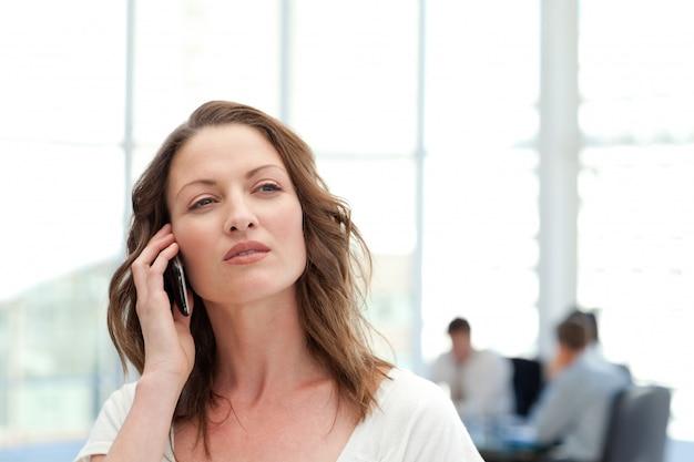 Empresaria atractiva en el teléfono mientras su equipo está trabajando