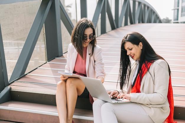 Empresaria ayudando a su colega mientras trabaja en la computadora portátil al aire libre