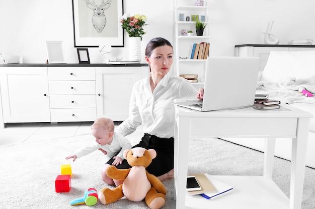 La empresaria con baby boy en una alfombra trabajando desde casa usando la computadora portátil