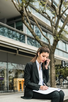 Empresaria bastante joven que habla en el teléfono mientras que escribe sobre carpeta en al aire libre