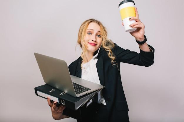 Empresaria bastante rubia con ordenador portátil, carpeta, caja, caffee en manos hablando por teléfono aislado. usar traje de oficina, estar ocupado, trabajo, éxito