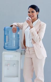 Empresaria bebiendo de un enfriador de agua