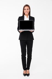 Empresaria bonita alegre que muestra la pantalla de la computadora portátil