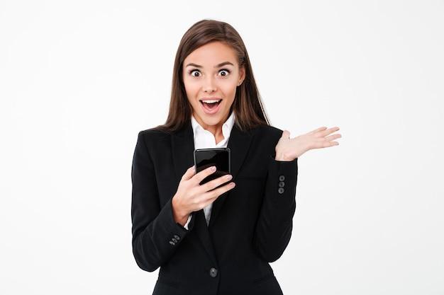 Empresaria bonita sorprendida chateando por teléfono.