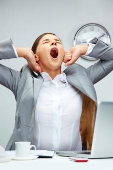 Empresaria bostezando en la oficina