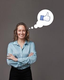 Empresaria con brazo cruzado sonriendo en gris pensando en un icono similar.