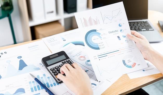 Empresaria con calculadora que controla el concepto de éxito de las estadísticas de la estrategia financiera de la empresa de análisis de documentos de análisis y la planificación para el futuro en la sala de oficina.
