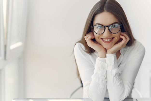 Empresaria en una camisa blanca sentada en la oficina