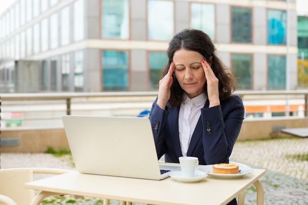 Empresaria cansada usando laptop en café al aire libre
