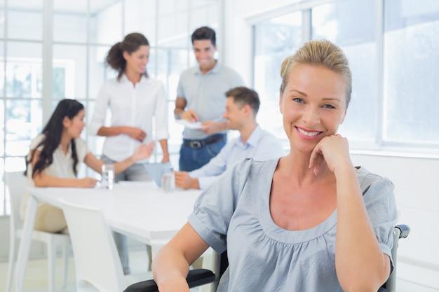 Empresaria casual en silla de ruedas sonriendo a la cámara con equipo detrás de ella