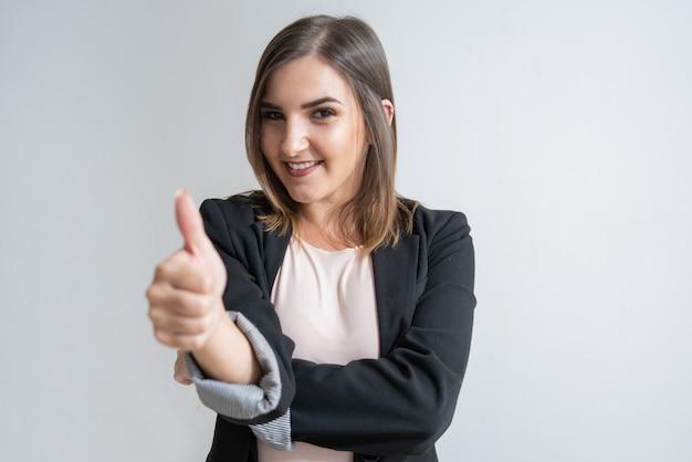 Empresaria caucásica joven positiva que muestra el pulgar para arriba