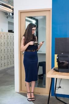 Empresaria caucásica de pie con beber café caliente y sosteniendo el teléfono celular en la pausa para el café en la oficina moderna