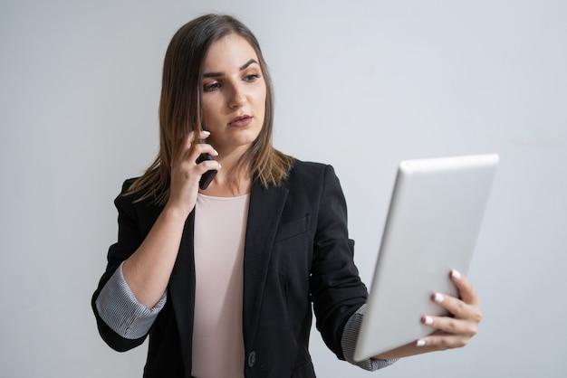Empresaria caucásica con el teléfono sosteniendo la tableta