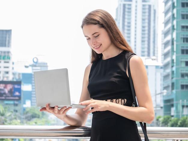 Empresaria caucásica usando una computadora portátil y sonriendo mientras está de pie en la oficina moderna en el centro de la ciudad