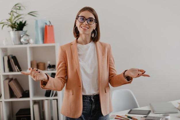 Empresaria en chaqueta rosa con sonrisa en oficina espaciosa blanca.