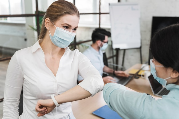 La empresaria con codo de máscara médica saludando a su colega