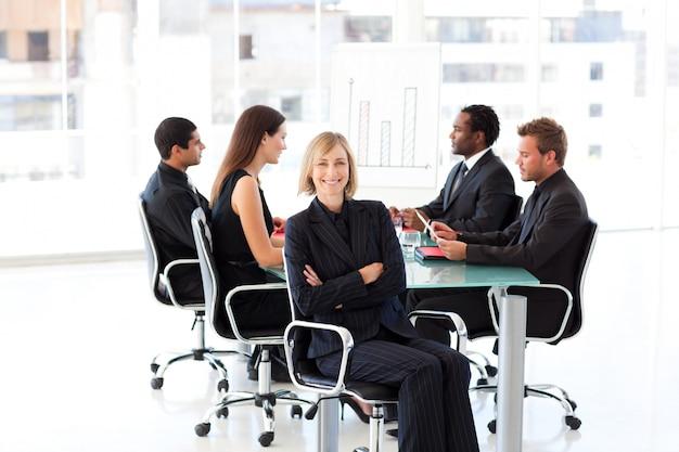 Empresaria cofre sentado con los brazos en una reunión
