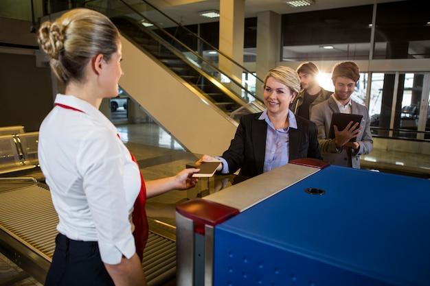 Empresaria en cola recibiendo pasaporte y tarjeta de embarque