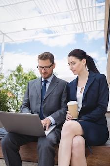 Empresaria y colega usando laptop