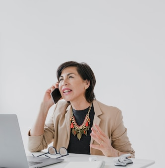 Empresaria con collar hablando por teléfono