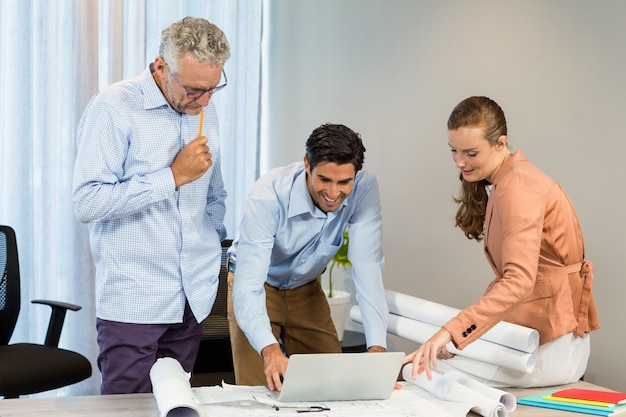 Empresaria y compañeros de trabajo discutiendo blueprint usando laptop