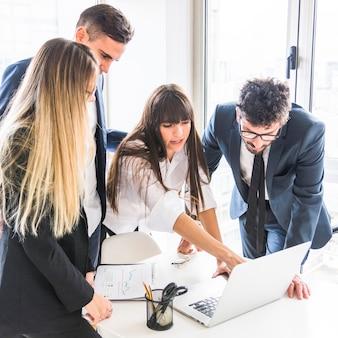 Empresaria compartiendo sus ideas creativas con su colega usando laptop