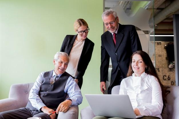 Empresaria confiada sonriente que muestra el ordenador portátil a su compañero de trabajo en la oficina