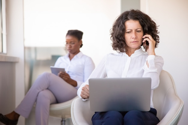 Empresaria confundida hablando por teléfono