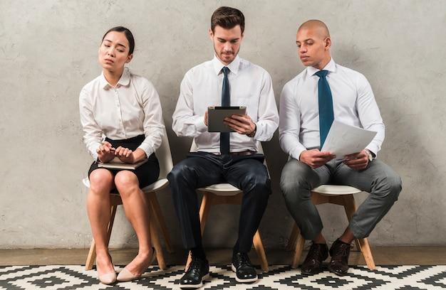 Empresaria corporativa curiosa interesada que mira a la tableta digital de los colegas