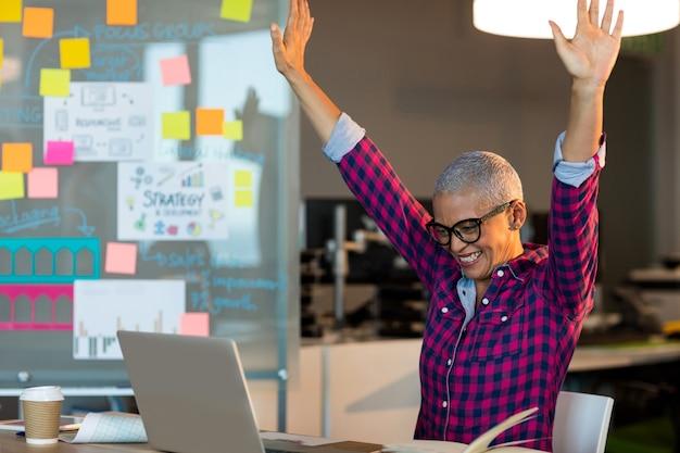 Empresaria creativa celebrando en el escritorio en la oficina