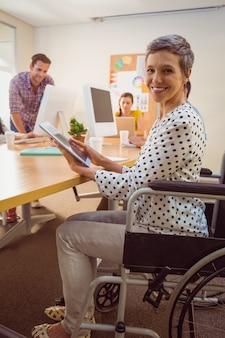 Empresaria creativa en silla de ruedas usando una tableta