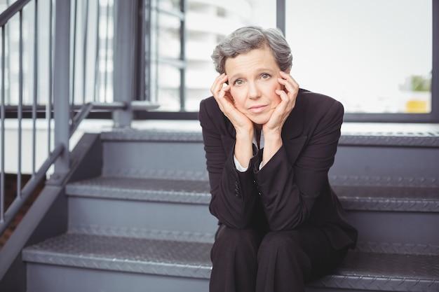 Empresaria deprimida pensativa que se sienta en pasos