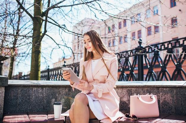 Empresaria en descanso en el parque. mujer de negocios profesional joven que usa la tableta al aire libre. modelo de mujer caucásica.