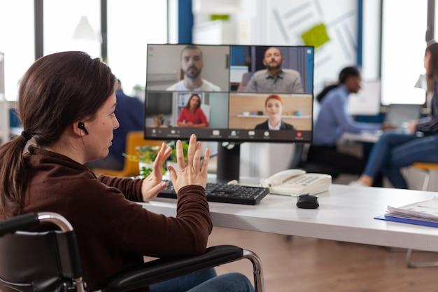 Empresaria discapacitada en silla de ruedas con conferencia de reunión de videollamada en línea