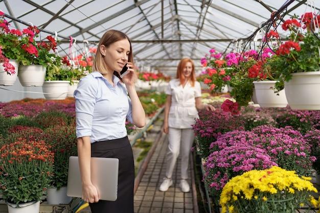 Empresaria discutiendo por teléfono una propuesta. ella sostiene una computadora portátil en una casa verde con flores.