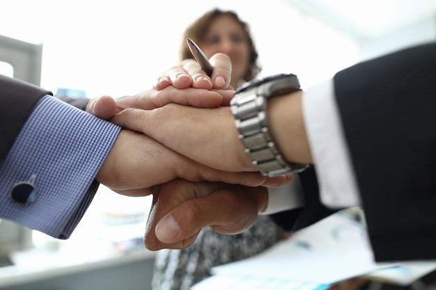 La empresaria y dos hombres de negocios cruzaron sus manos juntas en primer plano de la oficina