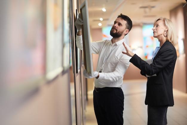 Empresaria eligiendo pintura en la galería de arte