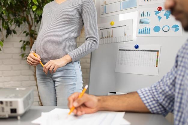 Empresaria embarazada con compañero de trabajo masculino durante una presentación
