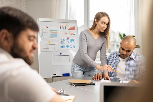 Empresaria embarazada con compañeros de trabajo masculinos durante una presentación
