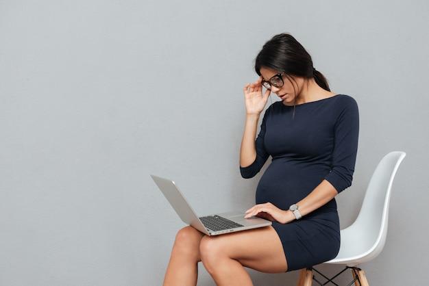 Empresaria embarazada concentrada que usa la computadora portátil