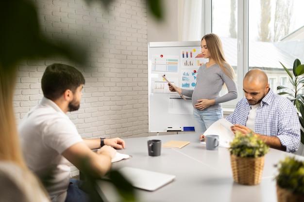 Empresaria embarazada dando presentación mientras compañeros de trabajo toman notas
