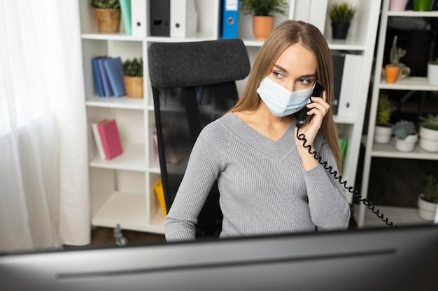 Empresaria embarazada hablando por teléfono mientras usa máscara médica