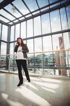 Empresaria embarazada hablando por teléfono móvil cerca del corredor