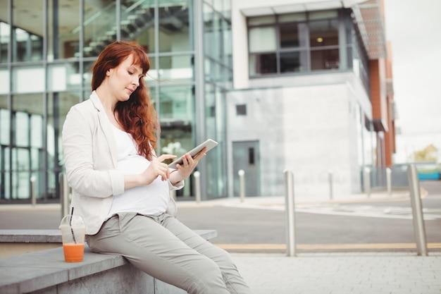 Empresaria embarazada con tableta digital
