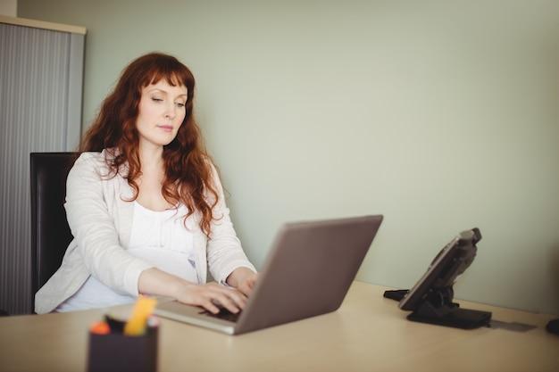 Empresaria embarazada usando laptop