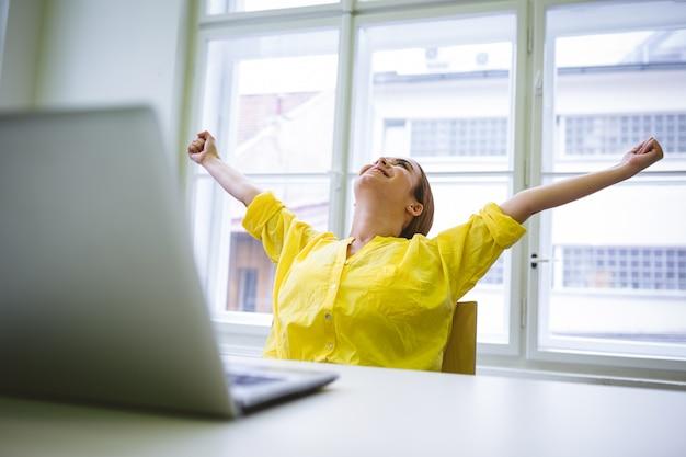 Empresaria emocionada con los brazos extendidos en la oficina