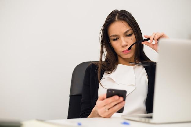 Empresaria emocionada que gana después de un logro leyendo un teléfono inteligente sentado en un escritorio en la oficina