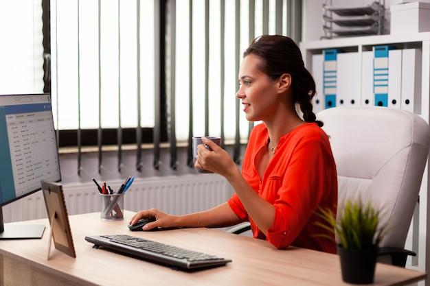 Empresaria empresaria concentrada mirando la pantalla del ordenador en el lugar de trabajo de la oficina. mujer segura de éxito en marketing sentado en el escritorio en el lugar de trabajo usando la computadora.